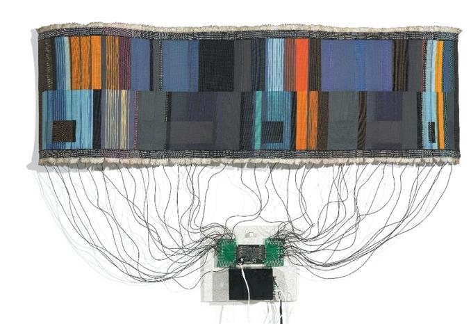 Kilim Devreler ::: Mühendis ve sanatçı Maggie Orth, Uluslararası Moda Makineleri'nin yöneticisi. Bu şirket elektronik tekstil konusunda uzman. Resimde ısıya duyarlı termokromik mürekkep ile basılmış kilim görüyorsunuz. Elektrik onlar aracılığıyla kullanıldığında, koyu renkten açık renklere doğru renk değiştiriyorlar.